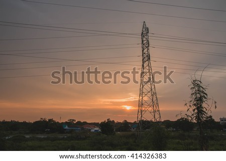 silhouette of high voltage electric tower with beautiful sunset background