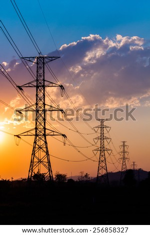 silhouette of high voltage electrical pole structure and sunset background