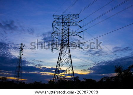 silhouette of high voltage electricity tower and telecommunication tower at sunset
