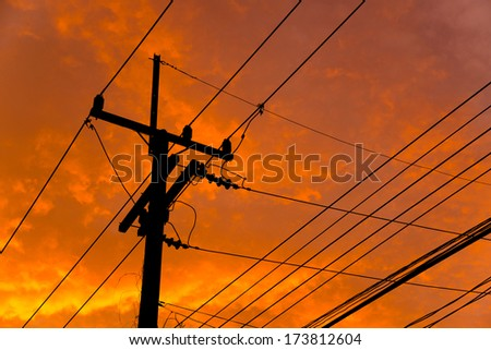 Silhouette of high voltage power lines against orange colorful s - stock photo