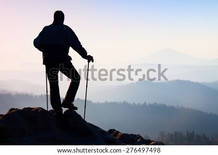 Silhouette of hiker with poles in hand. Hiker take a rest on rocky view point above misty valley. Sunny spring daybreak in rocky mountains.