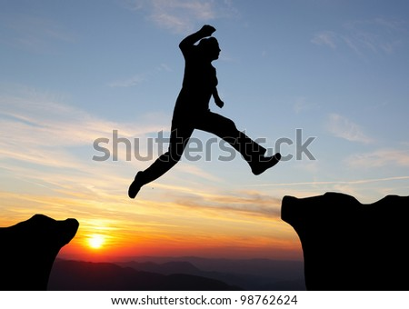 Silhouette of hiking woman jumping over the mountains at sunset - stock photo