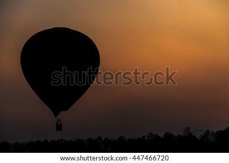 Silhouette of hot air balloon on bright orange sunset