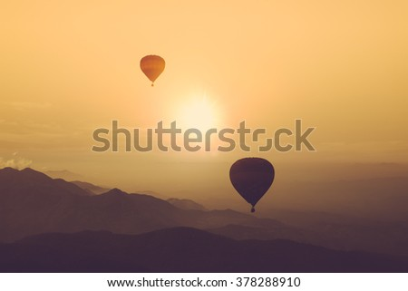Silhouette of hot air balloon over mountain vintage color - stock photo