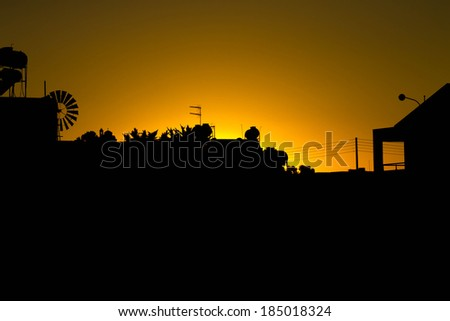 silhouette of houses with a church during the sunset - stock photo