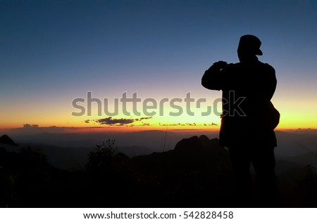 Silhouette of human scale traveler watch scenic sunset sunrise landscape view on mountain ridge.