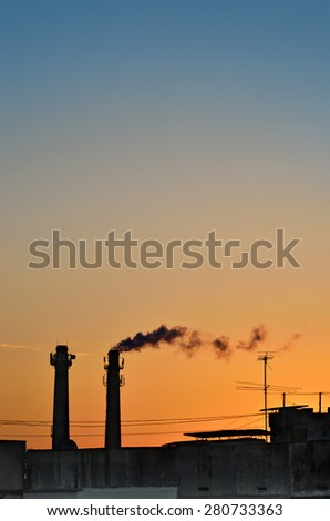 Silhouette of industrial production, polluting the atmosphere