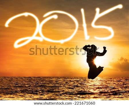 Silhouette of joyful woman jumping on beach celebrate new year 2015 - stock photo