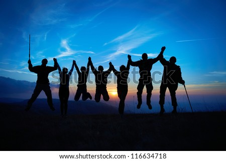 Silhouette of jumping friends in sunset against blue sky
