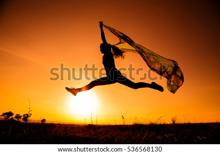 silhouette of  jumping girl on hill against sunset