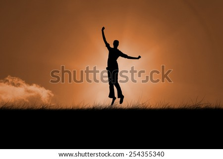 Silhouette of jumping woman against sunrise - stock photo