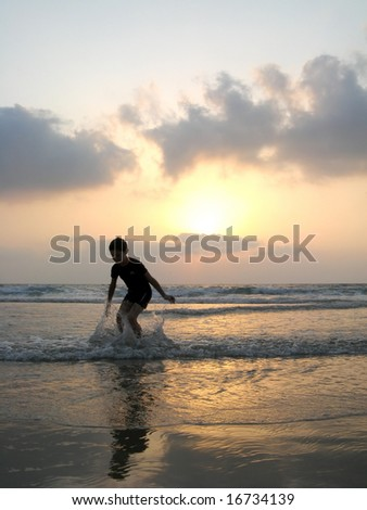 silhouette of kid on the beach at sunset - stock photo