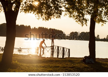 Silhouette of kids jumping from river dock - stock photo