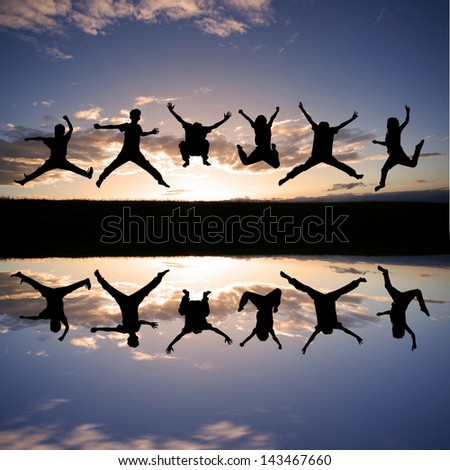 silhouette of kids jumping in sunset  - stock photo
