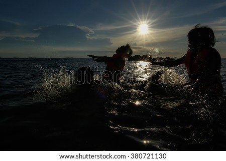 silhouette of kids playing on the sea before the sun.  The flare is intentionally plan to show the mood.