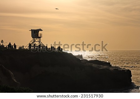 Silhouette of lifeguard tower and people on cliff at La Jolla Cove, San Diego, California. People enjoying view of the calm water. Orange sky. Late afternoon backlit ocean scene. Copy space.  - stock photo
