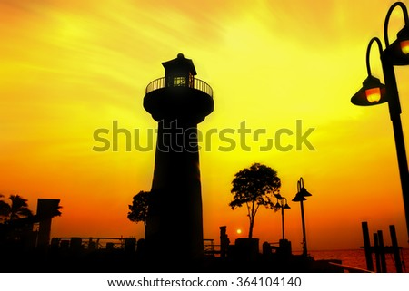 Silhouette of lighthouse and sunset behind. - stock photo