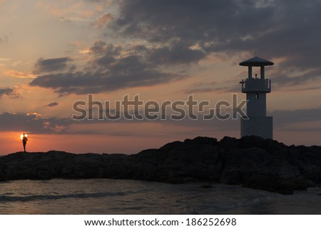 Silhouette of lighthouse with a man on the coast with seascape at sunset