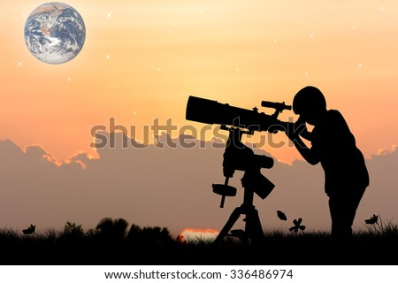 silhouette of little boy looking through a telescope at sunset  background,the backdrop of the planet earth. Elements of this image furnished by NASA.