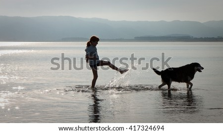 silhouette of little girl with dog playing in the sea at sundown, Opoutama Beach, Mahia Peninsula, East Coast, North Island, New Zealand