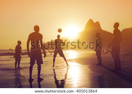 Silhouette of locals playing ball game at sunset in Ipanema beach, Rio de Janeiro, Brazil. - stock photo