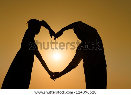 Silhouette of loving couple holding hands in heart shape over orange sunset background