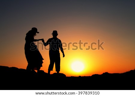 Silhouette of loving couple walking on a hill against the sun