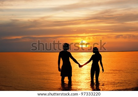 Silhouette of male and woman in sea against sunset. - stock photo