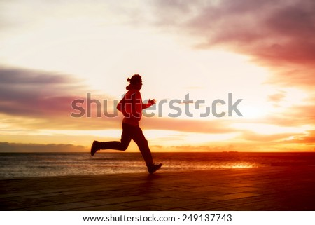 Silhouette of male athletic man running fast along seashore with amazing sky view on background