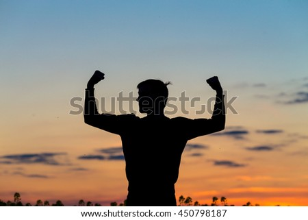 Silhouette of male celebrating with arm up towards the sunrise