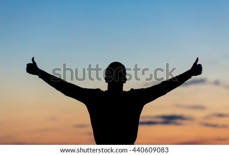 Silhouette of male celebrating with arm up towards the sunrise. Achievement concept.