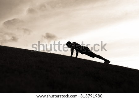 Silhouette of male doing push ups.  - stock photo
