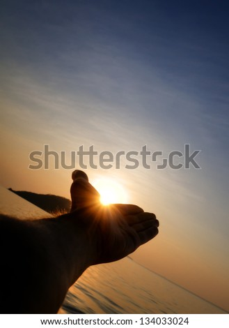 Silhouette of male hand catching sun - stock photo