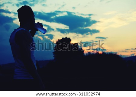 Silhouette of male jogger drinking water while enjoying the sunset with copy space area  for your text message or content, muscular build sportsman taking break after physical exercises in the park - stock photo