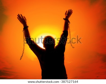 Silhouette of man agains the sunset ssky raising up his hands as he becomes free from chains and shackles - stock photo