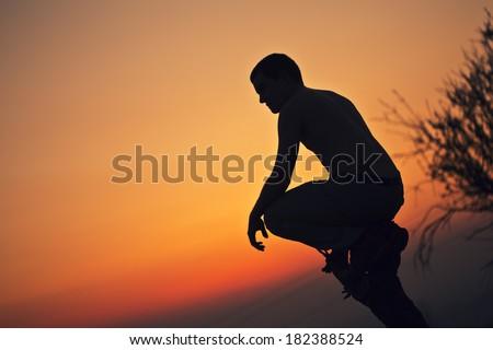 Silhouette of man and big sun. Conceptual scene. - stock photo