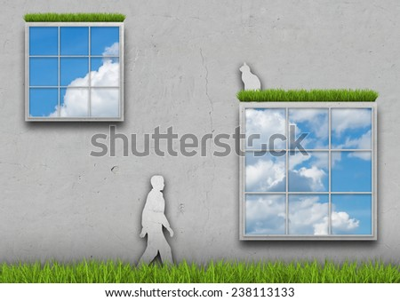 Silhouette of man and cat in the grass amid the concrete wall with windows