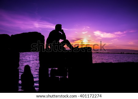 Silhouette of man and girl sitting at sunset - stock photo