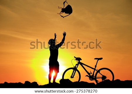 Silhouette of man and his bike in action throwing bag above his head on rock mountain with sunrise twilight background. Symbol of relax, success and touring. - stock photo