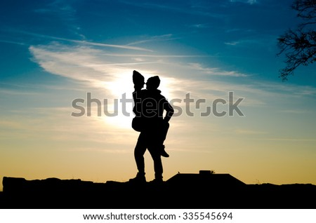 Silhouette of man and woman at sunset abstract blue clouds