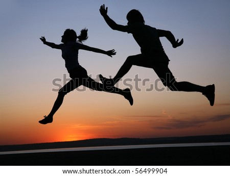 silhouette  of man and  woman run together on a sunset on lake coast - stock photo