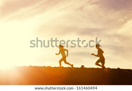 Silhouette of Man and woman running together into sunset, Wellness fitness concept - stock photo