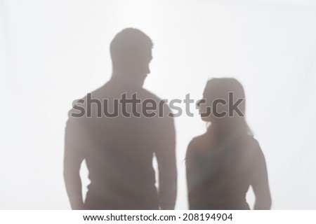Silhouette of man and woman standing on white background and looking at each other - stock photo
