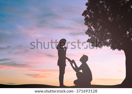 silhouette of man ask woman to marry/engage at nature park background:teen couple in love concept:dark shadow of people lovers in romantic and happy moment time.Valentine's day:pastel tone of backdrop - stock photo