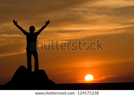 Silhouette of man at the sunset. Emotions of success and pleasure