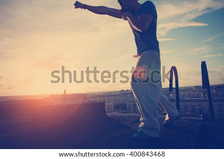 Silhouette of man boxing with shadow on the roof at sunset (intentional sun flare and vintage color)