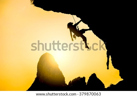 Silhouette of man climbing at sunset. Extreme sport concept