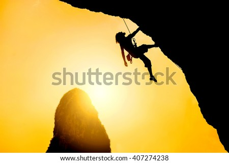 Silhouette of man climbing at sunset. Extreme sport concept - stock photo