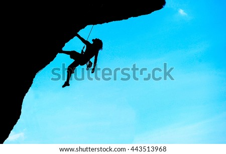 Silhouette of man climbing at sunset. The rock climber during rock conquest. Climbing sport concept.  - stock photo