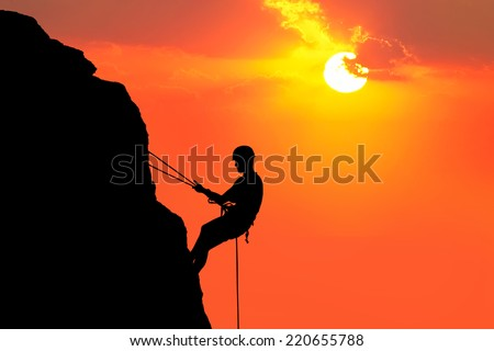 Silhouette of man climbing on rock (mountain) at sunset - stock photo